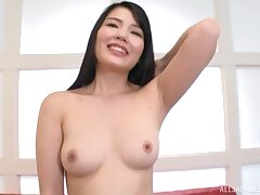 Coy Japanese babe takes off her duds and fingers her stained pussy